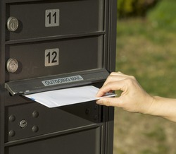 photo of female hand putting letter into outgoing postal mailbox with green grass in background