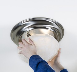 Photo of female hands installing glass lid over new light bulbs with white ceiling in background