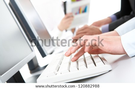 Photo of female hands typing on computer keyboard in working environment