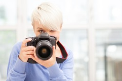 photo of Female photographer with DSLR at home sitting on the floor