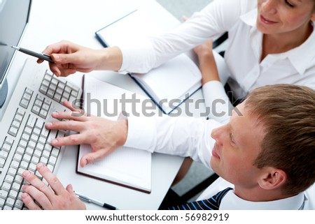 Photo of female pointing at monitor with typing man near by during discussion - stock photo