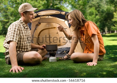 Photo of female tasting soup while her boyfriend looking at her in the park on sunny day