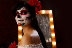 Photo of female witch with body painting on face on background of mirror
