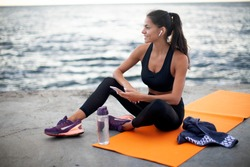 Photo of fit young woman sitting on orange yoga mat outdoors by the sea, holding the phone in one hand, listening to music on wireless headphones, looking away and smiling, wearing black sports wear