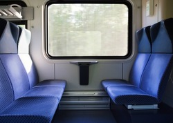 photo of Five blue seats facing each other in modern European train