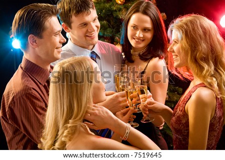 Photo of five smiling friends touching their glasses with each other at christmas