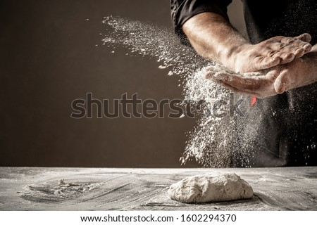 Photo of flour and men hands with flour splash. Cooking bread. Kneading the Dough.