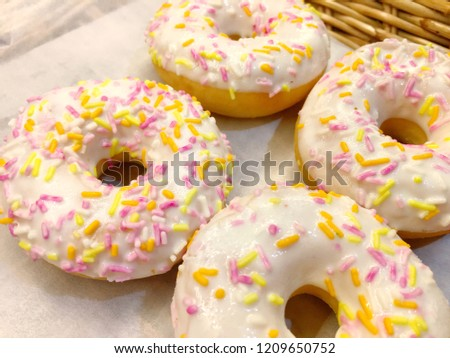 Photo of Four pieces of donut with white sugary and sprinkles #1209650752