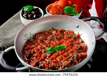 photo of fresh cooked tomato sauce with olives and basil