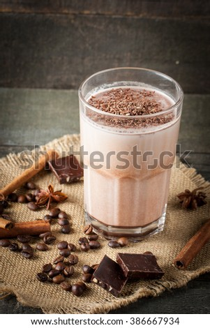 Photo of fresh Made Chocolate Banana Smoothie on a wooden table with coffee and spices. Selective focus. Milkshake. Protein diet. Healthy food concept. Drink, coffee beans, chocolate, cinnamon, anise. #386667934