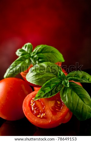 photo of fresh sliced tomatoes with basil on glass table with spot light
