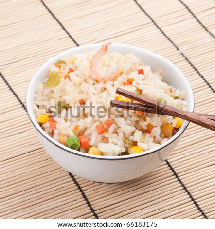 Photo of fried rice dish represented on table in restaurant. Delicious porridge with different vegetables, prawn and seafood in plate.
