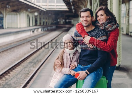 Photo of friendly family have good relationship, have trip during vacation, pose at platform of railway station. Lovely woman embrace husband, their small daughter stands near parents near luggage #1268339167