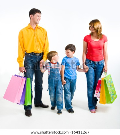 Photo of friendly family walking with shopping bags over white background