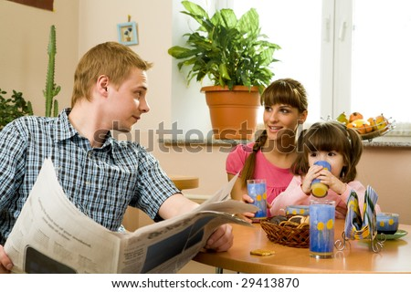 Photo of friendly woman speaking to her husband in the kitchen while he reading paper and their daughter drinking juice