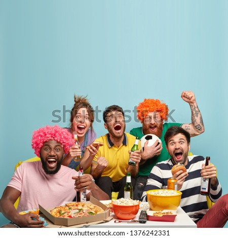 Photo of friends watch soccer game, celebrate goal, clench fists, enjoy watching sport competition, have delicious snack, drink cold beer, spend spare time at home. Pastime and entertainment