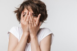 Photo of frightened woman with short brown hair in basic t-shirt keeping hands over her face and looking at camera isolated over white background