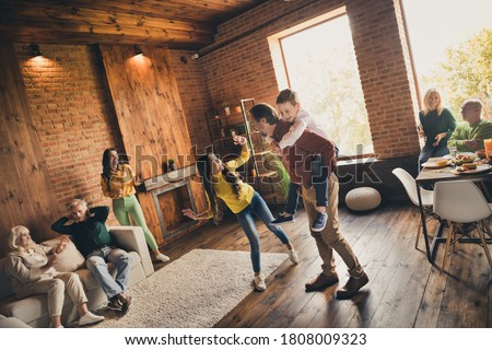 Photo of full big family eight people gathering two little kids play dad piggyback grandparents sitting sofa dinner table drink wine talk generation in home evening living room indoors Stockfoto ©