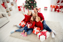 Photo of full big family five people gathering three small kids hold gifts bow ribbon mom make shoot selfie, wear red jumper jeans in decorated living room x-mas tree lights indoors