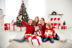 Photo of full big family five people meeting lovers three little kids hold gifts decorated bow ribbon daughter take shoot selfie wear red jumper jeans in home living room x-mas tree indoors