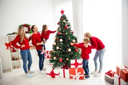 Photo of full big family five people meeting three little kids dad hold daughter decorate x-mas tree toys balls star wear red jumper jeans in home living room gift boxes indoors
