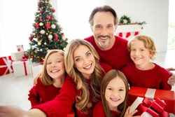 Photo of full big family five people meeting three little kids hold present box bow ribbon mom make shoot selfie wear red jumper in living room x-mas tree lights many gifts indoors