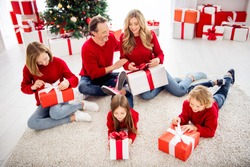 Photo of full big family five people meeting three small kids lie floor carpet unboxing presents wear red jumper jeans in decorated living room x-mas tree many boxes lights indoors
