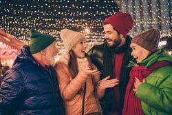 Photo of full big family four members x-mas meeting gathering hug talk crazy news see santa deer sledge outerwear knitted headwear scarf coat evening street walk illumination outside
