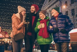 Photo of full big family four members x-mas meeting gathering tell funny noel atmosphere joke laugh advent outerwear knitted hat scarf coat night street walk illumination outside
