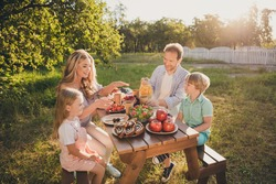 Photo of full big family four people gathering sit bench relax breakfast table drink citrus juice eat fruits vegetables salad generation warm weather comfort home park backyard outdoors