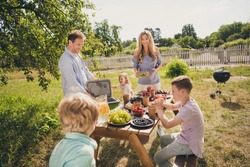 Photo of full big family gathering five people dad make ice meat grill mom hold salad small kids play around served lunch table barbecue sunny summer day green house garden backyard outdoors
