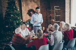 Photo of full big family gathering sit dinner table father guy telling x-mas toast multi-generation eight members harmony in newyear decorated living room indoors
