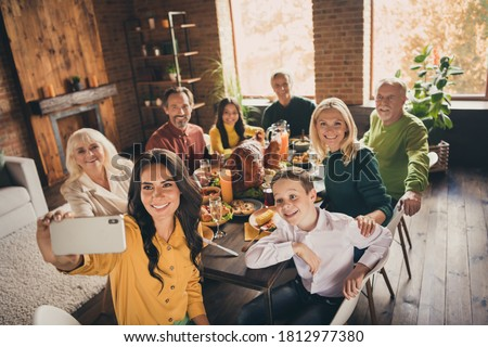 Photo of full family gathering eight people woman mother hold telephone make shoot selfie harmony peaceful day served dinner big table turkey generation in home evening living room indoors