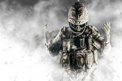 Photo of fully equipped soldier in heavy level 3 amor ammunition standing in white smoke.