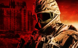 Photo of fully equipped soldier in heavy level 3 armor ammunition standing on red destructed city battlefield background.