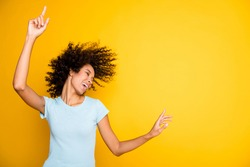 Photo of funky cute dark skin curly girl dressed blue t-shirt dancing pointing empty space isolated yellow color background