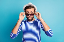 Photo of funky excited handsome guy tourist taking off cool black sun specs open mouth read discounts banner wear striped sailor shirt cap isolated blue color background