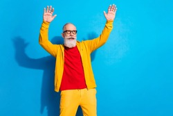 Photo of funky funny smiling mature man in glasses dancing having fun wear yellow suit isolated on blue color background