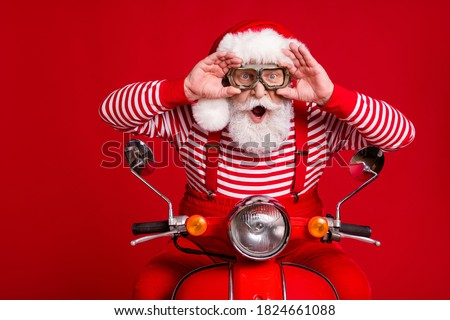 Photo of funky retired old man moped ride open mouth hold eyewear incredible speed wind wear santa x-mas costume suspenders sunglass boots striped shirt cap isolated red color background