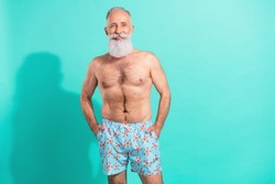 Photo of funny attractive pensioner shirtless smiling arms pockets isolated teal color background