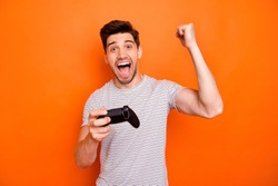 Photo of funny crazy astonished guy hold hands joystick playing video games excited gamer came finish first raise fist wear striped t-shirt isolated bright orange color background