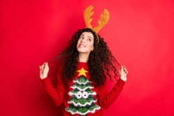 Photo of funny curly lady dreaming x-mas would bring peace and love to all people on earth looking empty space wear head horns pullover isolated red color background