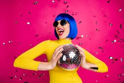 Photo of funny excited lady student party nightclub hold disco ball dancing queen confetti fall wear retro specs yellow turtleneck blue short wig isolated bright pink color background
