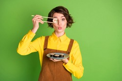 Photo of funny girl hold chopsticks plate sushi hide eye with roll pout lips wear yellow shirt overall isolated green color background