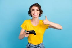 Photo of funny girl hold joystick raise thumb up toothy smile wear yellow t-shirt isolated blue color background