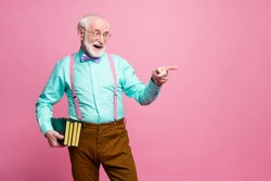Photo of funny grandpa professor books university college direct finger empty space choose student for answer wear specs shirt suspenders bow tie pants isolated pink pastel color background
