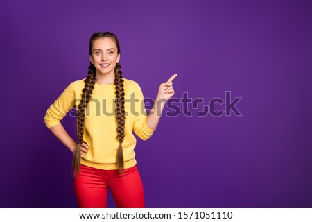 Photo of funny lady long braids hairdo indicating finger empty space advising cool shopping prices wear casual yellow pullover red trousers isolated purple color background