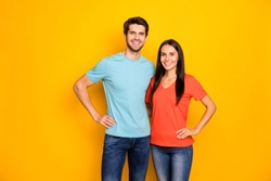 Photo of funny lovely two people couple guy and lady hugging hands by sides one best team wear casual blue orange t-shirts jeans isolated over yellow color background