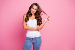 Photo of funny pretty wavy lady wind curl around finger showing perfect groomed hairstyle after treatment procedure wear white casual tank-top jeans isolated pink color background