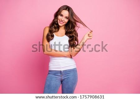 Photo of funny pretty wavy lady wind curl around finger showing perfect groomed hairstyle after treatment procedure wear white casual tank-top jeans isolated pink color background Foto stock ©
